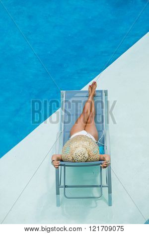 woman suntanning enjoying on sunbed at swimming pool
