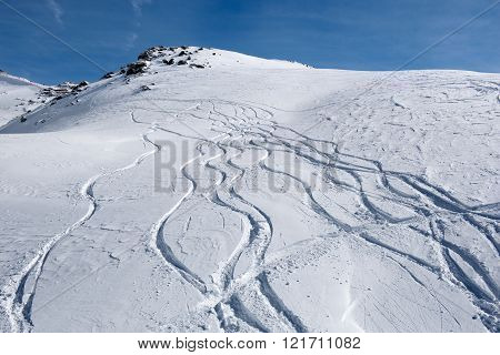 Multiple tracks running down in the snow on the mountain slopes