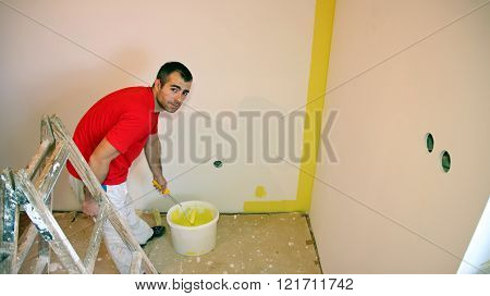 Painter Painting A Wall With A Paint Roller
