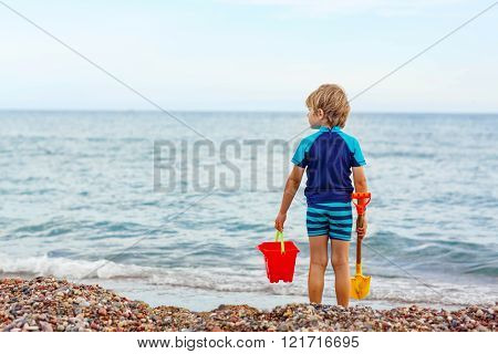 little blond kid boy standing on lonely ocean beach