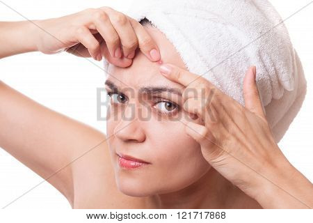 close up portrait of a girl with a towel on her had squeezing pimple