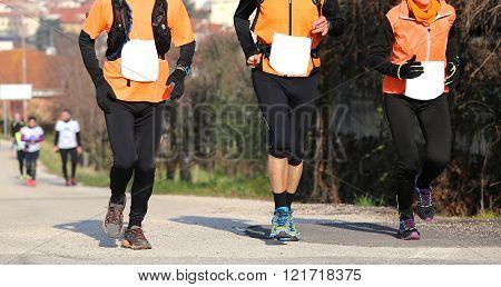 Three Runners Run On Asphalt Road Outdoors