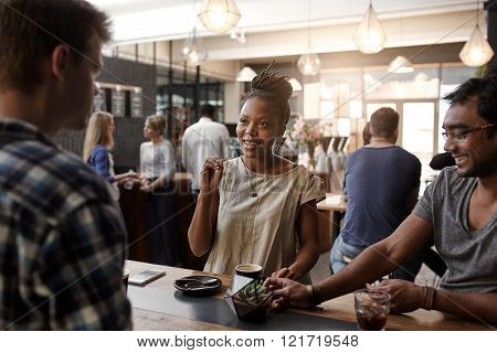 Entrepreneurial African woman smiling and gesturing during a meeting in a busy modern coffee shop with two men