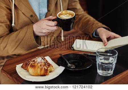 Cropped shot of a woman sitting at a modern cafe holding a cappucino and reading notes in her notebook
