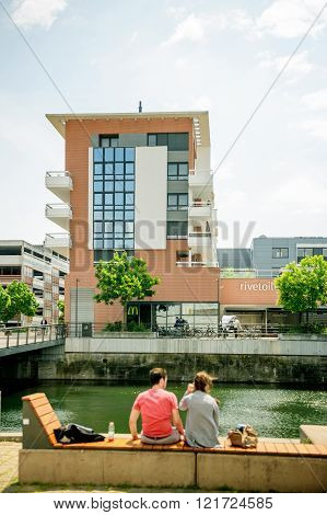 STRASBOURG FRANCE - MAY 23 2015: Young couple admiring the water canal on Presqu'Ile Malraux vis-a-vis of the Rivetoille Shopping and Leisure center in the city of Strasbourg Alsace