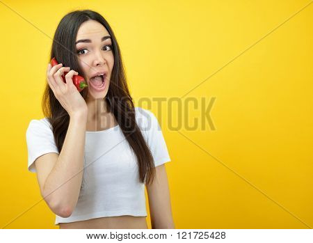 Hipster girl holding chili pepper near her face  like smartphones and shouting over yellow background.