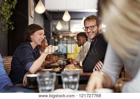 Portrait of a man turning to smile at the camera while on a coffee date with his laughing girlfriend in a busy modern cafe