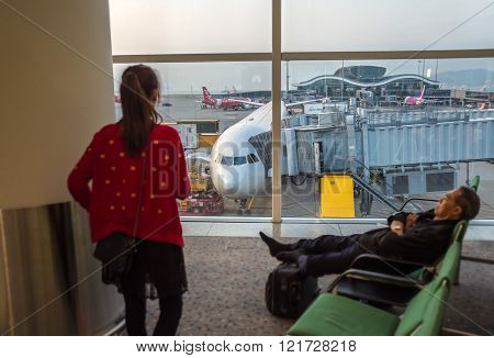 Hong Kong, China, 28Th February 2015. Two Asian Passengers Waiting For Their Flight With A Plane In
