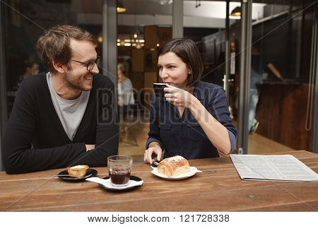 Young couple sitting at an outdoor table of a modern cafe, the boyfriend smiling at his girlfriend as she is taking a sip of her coffee