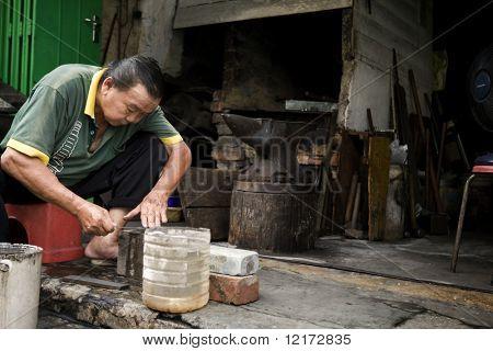 Malaca - 31 de octubre: Un Herrero afila un cuchillo que había hecho, es uno de los muy pocos livi