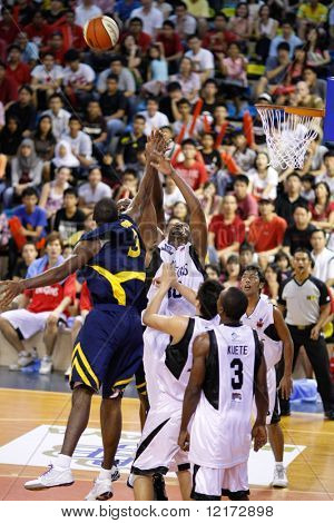 KUALA LUMPUR - DECEMBER 13: KL Dragons' Jamal Brown blocks a shot by Thailand Tigers' Chaz Briggs in the ASEAN Basketball League match. December 13, 2009 in Kuala Lumpur.