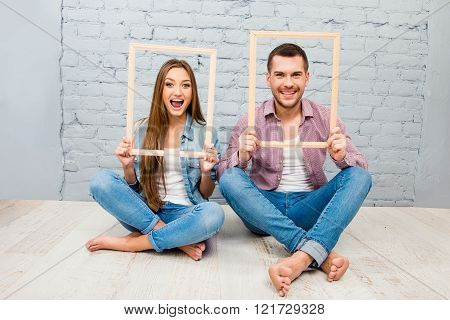 Cheerful couple in love sitting on the floor and holding wooden frames
