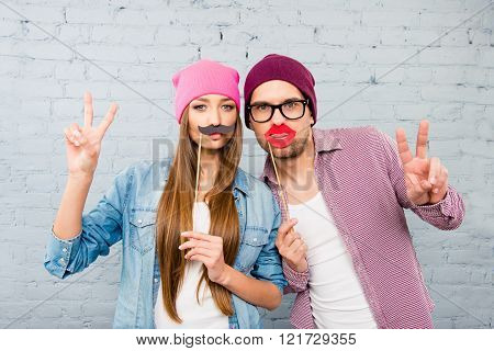 Man And Woman Holding Paper Props And Gesturing With Two Fingers