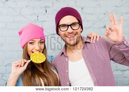 Pretty Woman Biting Lollipop And Her Man Gesturing