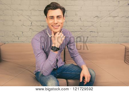 Portrait of cheerful man in  wristwatch sitting at home on sofa
