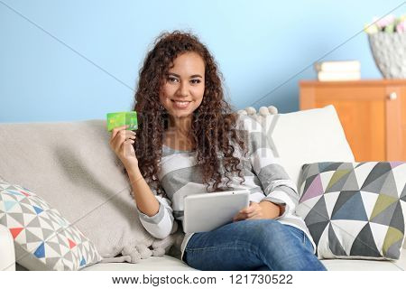 Beautiful young girl with credit card and tablet on couch