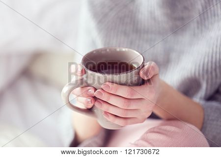 Woman in a grey sweater and warm socks holding a cup of tea while sitting on a white knitted blanket