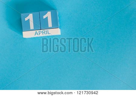 April 11th. Image of april 11 wooden color calendar on blue background.  Spring day, empty space for