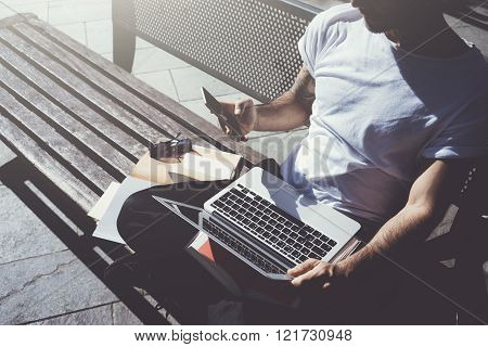 Photo man sitting city park bench and texting message smartphone. Using wireless internet. Studying