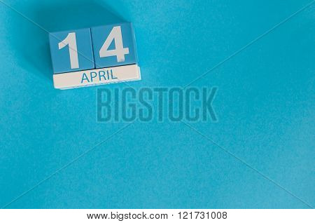 April 14th. Image of april 14 wooden color calendar on blue background.  Spring day, empty space for