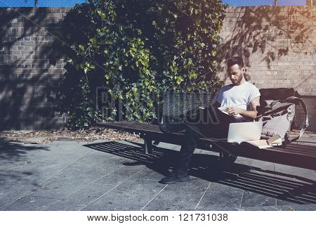 Photo bearded man wearing white tshirt sitting city park bench and reading book. Studying at the Uni