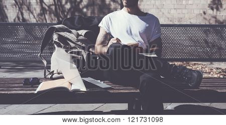 Photo bearded man wearing white tshirt sitting city park and writes message. Studying at the Univers