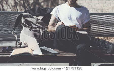 Student wearing white tshirt sitting city park and writes message. Studying at the University, worki