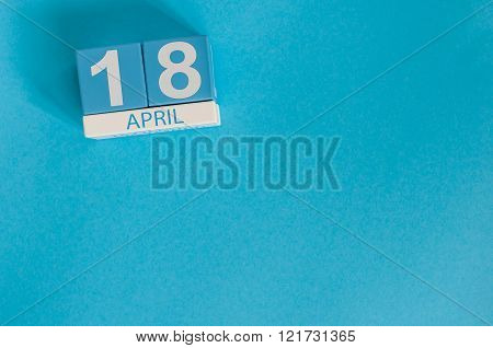 April 18th. Image of april 18 wooden color calendar on blue background.  Spring day, empty space for