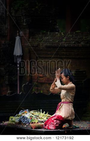 BALI - JANUARY 15: Balinese lady kneels down to pray at the Pura Tirta Empul, Tapaksiring January 15, 2010 in Bali, Indonesia.