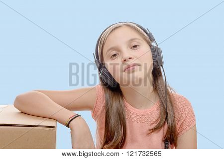 a preteen listening to music with headphones blue background