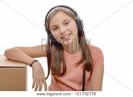 a preteen listening to music with headphones, on white