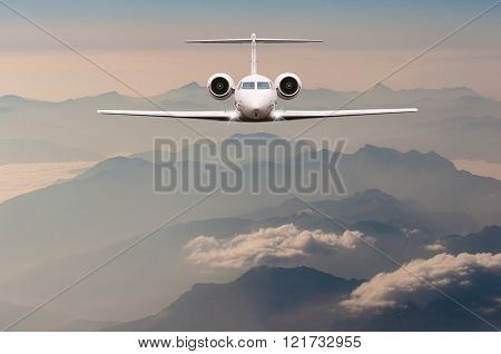 Luxury Airplane fly over clouds and Alps mountain on sunset. Front view of a big passenger or cargo