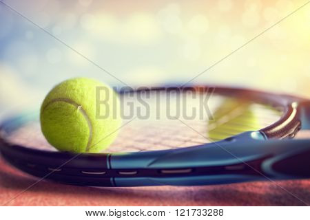 Tennis ball resting on top of a tennis racquet on a red asphalt court
