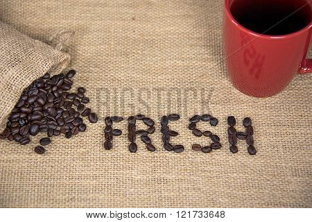 fresh coffee beans with red mug on burlap