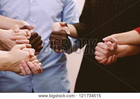 White caucasian and black afro american hands holding together, friendship concept