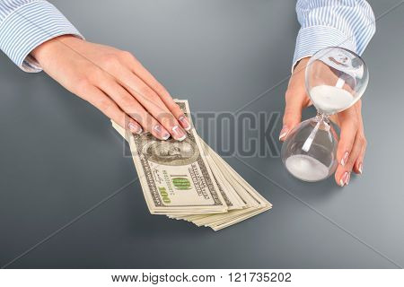 Woman touches hourglass and cash.