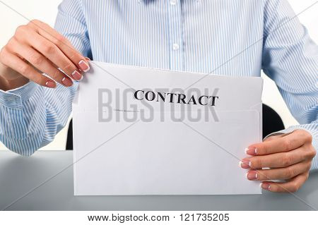 Woman takes contract from envelope.