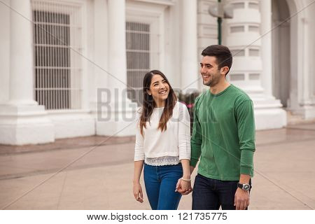 Pretty couple holding hands and walking