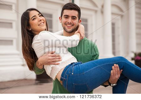 Young man carrying girlfriend and having fun