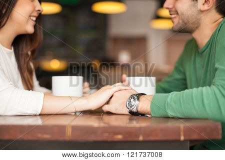 Cute Couple Holding Hands In A Restaurant