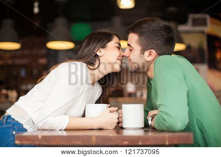 Cute Couple Kissing At A Cafe