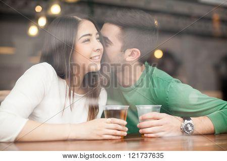 Man whispering in a girl's ear