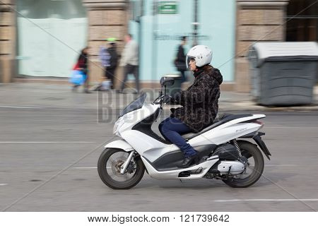 VALENCIA, SPAIN - MARCH 14, 2016: A woman riding a 2015 Honda PCX 150 scooter in the streets of Valencia. Originally developed in Thailand, the PCX is a popular commuter bike in Europe.