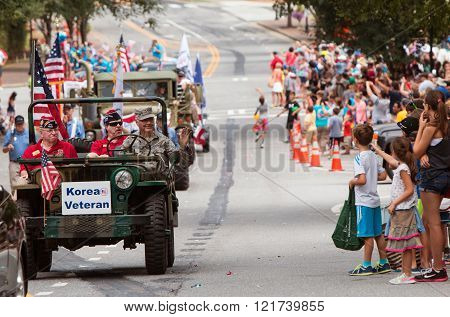 ALPHARETTA, GA - AUGUST 2015:  A Korean War veteran driving an army jeep waves to spectators attending the annual Old Soldiers Day Parade in Alpharetta GA on August 1 2015.