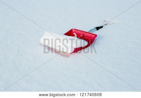 Red Shovel For Snow Removal Lying In The Snow