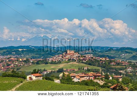 Small town on green heel under blue sky in Piedmont, Northern Italy.