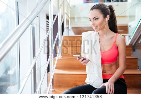 Happy charming young sportswoman sitting on stairs and listening to music from smartphone in gym