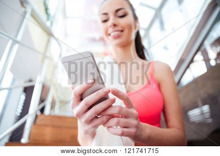 Smiling cute young sportswoman sitting and using mobile phone in gym