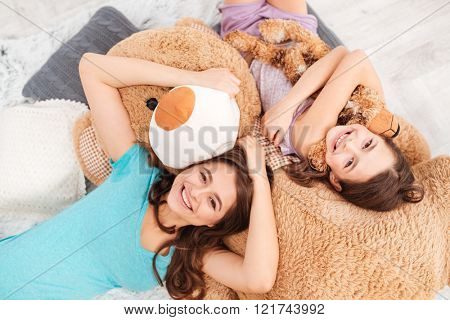 Cheerful cute sisters smiling and lying on soft plush bear at home