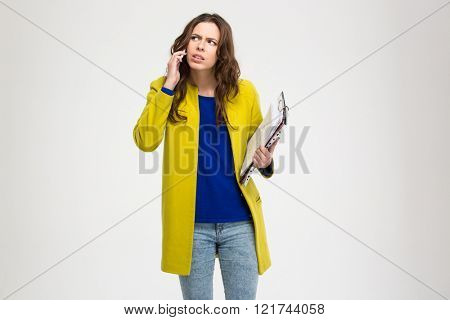 Thoughtful frowning young woman holding clipboard and using smartphone over white background
